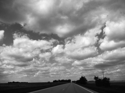 Summer clouds over a country road.